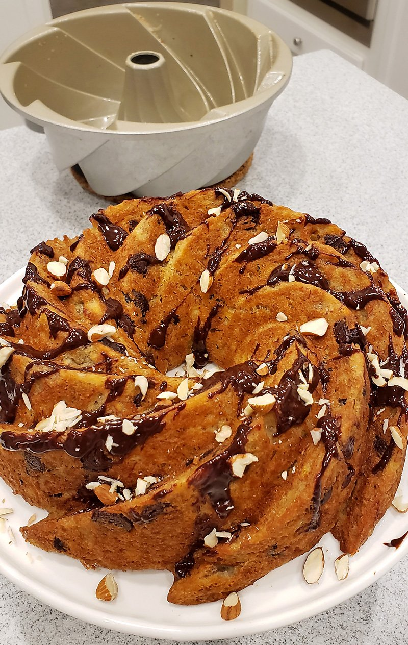 Banana Bundt Cake with melted Chocolate and nuts added on top after baking