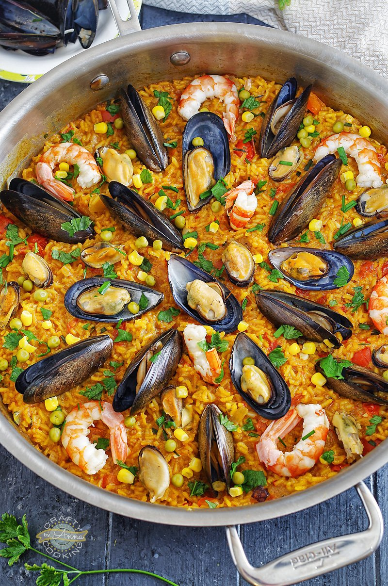 🥘 Seafood Paella! An easy version of the classic Spanish dish that is easy enough to prepare for a weeknight dinner, but delicious enough to serve to company.  #SeafoodPaella #Paella #Recipes #Cooking #CraftyCookingByAnna